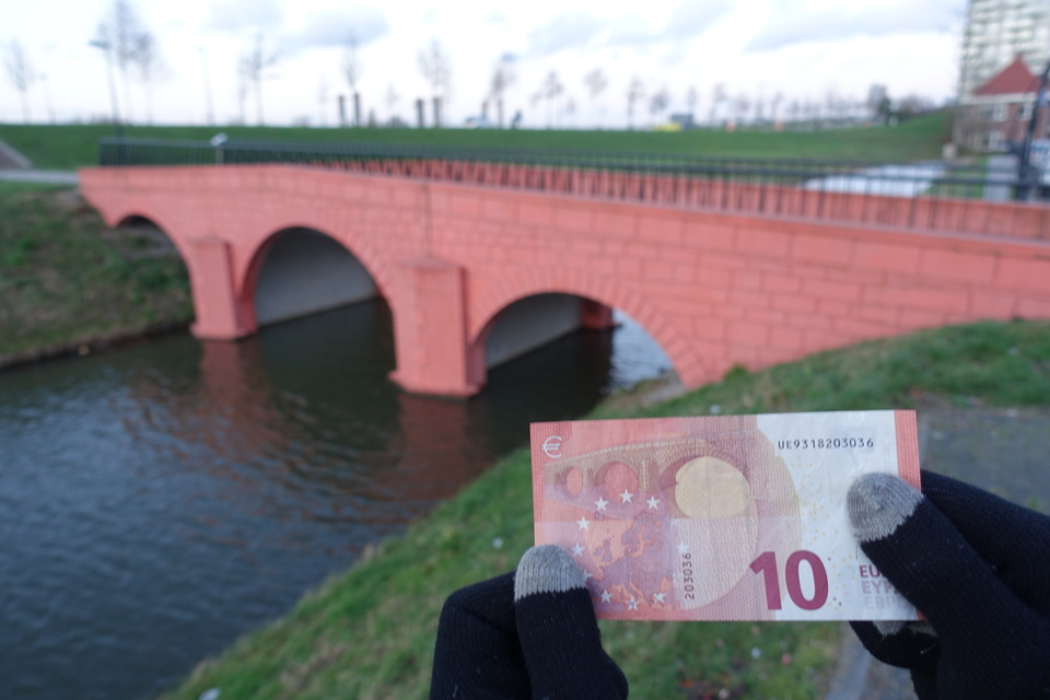 foreground: a euro note. background: the bridge from that note
